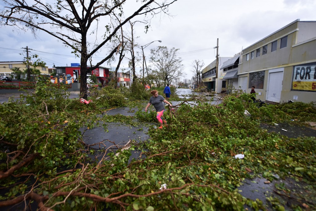 Residents clear fallen debris after the passage of Hurricane Maria, in San Juan, Puerto Rico, on September 20, 2017. Maria slammed into Puerto Rico on, cutting power on most of the US territory as terrified residents hunkered down in the face of the island's worst storm in living memory. After leaving a deadly trail of destruction on a string of smaller Caribbean islands, Maria made landfall on Puerto Rico's southeast coast around daybreak, packing winds of around 150mph (240kph).  / AFP PHOTO / HECTOR RETAMAL