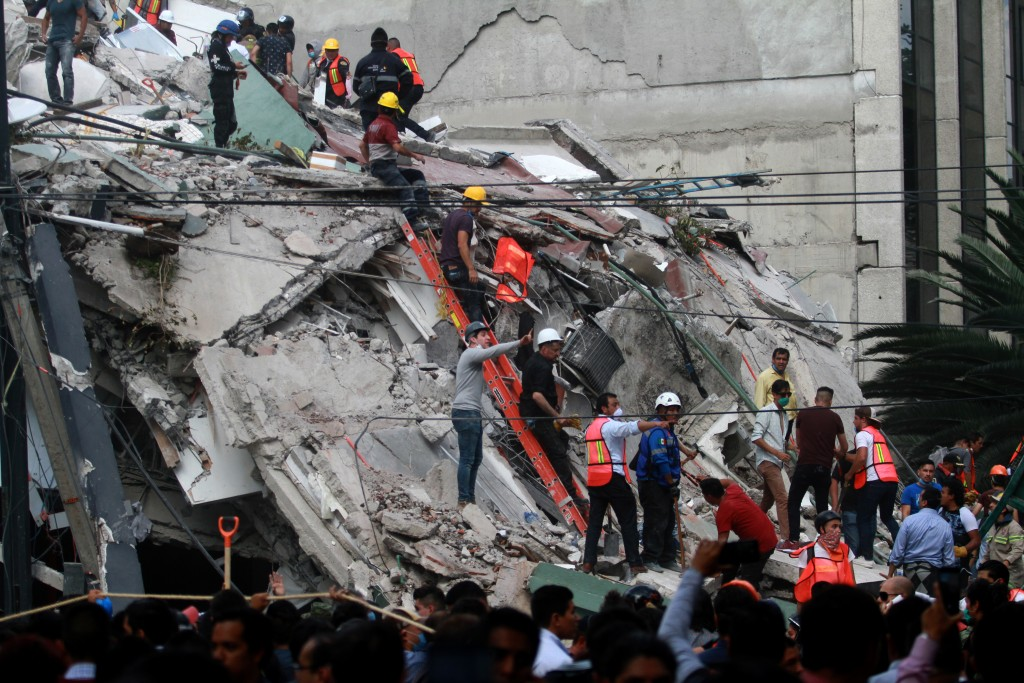 Rescuers and volunteers remove rubble and debris from a flattened building in search of survivors after a powerful quake in Mexico City on September 19, 2017. A powerful earthquake shook Mexico City on Tuesday, causing panic among the megalopolis' 20 million inhabitants on the 32nd anniversary of a devastating 1985 quake. The US Geological Survey put the quake's magnitude at 7.1 while Mexico's Seismological Institute said it measured 6.8 on its scale. The institute said the quake's epicenter was seven kilometers west of Chiautla de Tapia, in the neighboring state of Puebla. / AFP PHOTO / VICTOR CRUZ