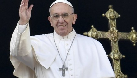 """Pope Francis waves from the balcony of St Peter's basilica during the traditional """"Urbi et Orbi"""" Christmas message to the city and the world, on December 25, 2016 at St Peter's square in Vatican. Pope Francis offered his thoughts to victims of terrorism in his annual Christmas address, days after the truck attack that left 12 dead at a festive Berlin market. / AFP PHOTO / ANDREAS SOLARO"""