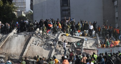 Rescuers, firefighters, policemen, soldiers and volunteers remove rubble and debris from a flattened building in search of survivors after a powerful quake in Mexico City on September 19, 2017. A devastating quake in Mexico on Tuesday killed more than 100 people, according to official tallies, with a preliminary 30 deaths recorded in the capital where rescue efforts were still going on. / AFP PHOTO / YURI CORTEZ
