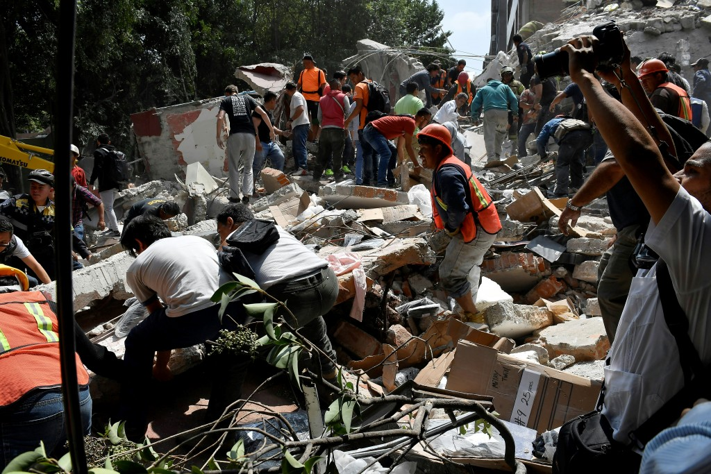 People remove debris of a building which collapsed after a quake rattled Mexico City on September 19, 2017. A powerful earthquake shook Mexico City on Tuesday, causing panic among the megalopolis' 20 million inhabitants on the 32nd anniversary of a devastating 1985 quake. The US Geological Survey put the quake's magnitude at 7.1 while Mexico's Seismological Institute said it measured 6.8 on its scale. The institute said the quake's epicenter was seven kilometers west of Chiautla de Tapia, in the neighboring state of Puebla. / AFP PHOTO / Omar TORRES