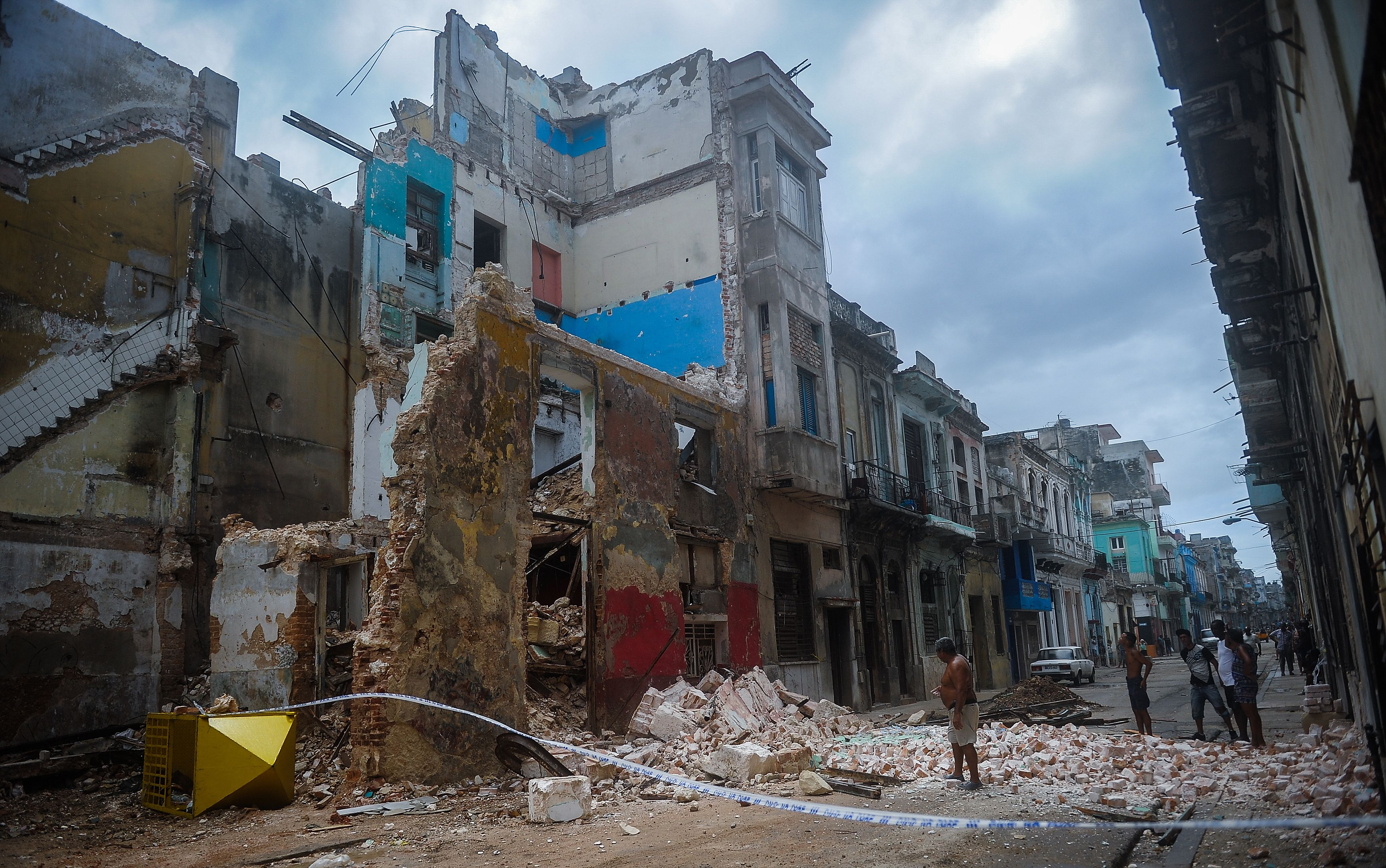 TOPSHOT - Cubans stand bt a collapsed building in Havana, on September 9, 2017.  Irma's blast through the Cuban coastline weakened the storm to a Category Three, but it is still packing 125 mile-an-hour winds (205 kilometer per hour) and was expected to regain power before hitting the Florida Keys early Sunday, US forecasters said. The Cuban government extended its maximum state of alert to three additional provinces, including Havana, amid fears of flooding in low-lying areas. / AFP / YAMIL LAGE