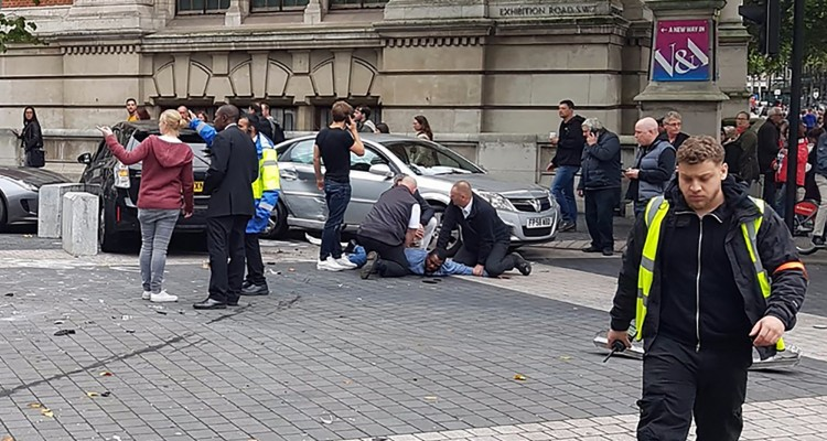 "A handout picture obtained from the twitter user @StefanoSutter shows a man being restrained alongside vehicles (centre R) on Exhibition Road, in between the Victoria and Albert (V&A) museum, and the Natural History Museum, in London on October 7, 2017, following an incident in South Kensington. Police arrested a man near London's Natural History Museum on Saturday after a vehicle apparently drove into pedestrians, injuring a number of people. Crowds in the busy tourist spot in South Kensington, which is also home to the Victoria & Albert Museum and the Science Museum, fled screaming in panic, an AFP reporter said. / AFP PHOTO / @StefanoSutter / Handout / RESTRICTED TO EDITORIAL USE - MANDATORY CREDIT ""AFP PHOTO / STEFANO SUTTER"" - NO MARKETING NO ADVERTISING CAMPAIGNS - DISTRIBUTED AS A SERVICE TO CLIENTS == NO ARCHIVE"