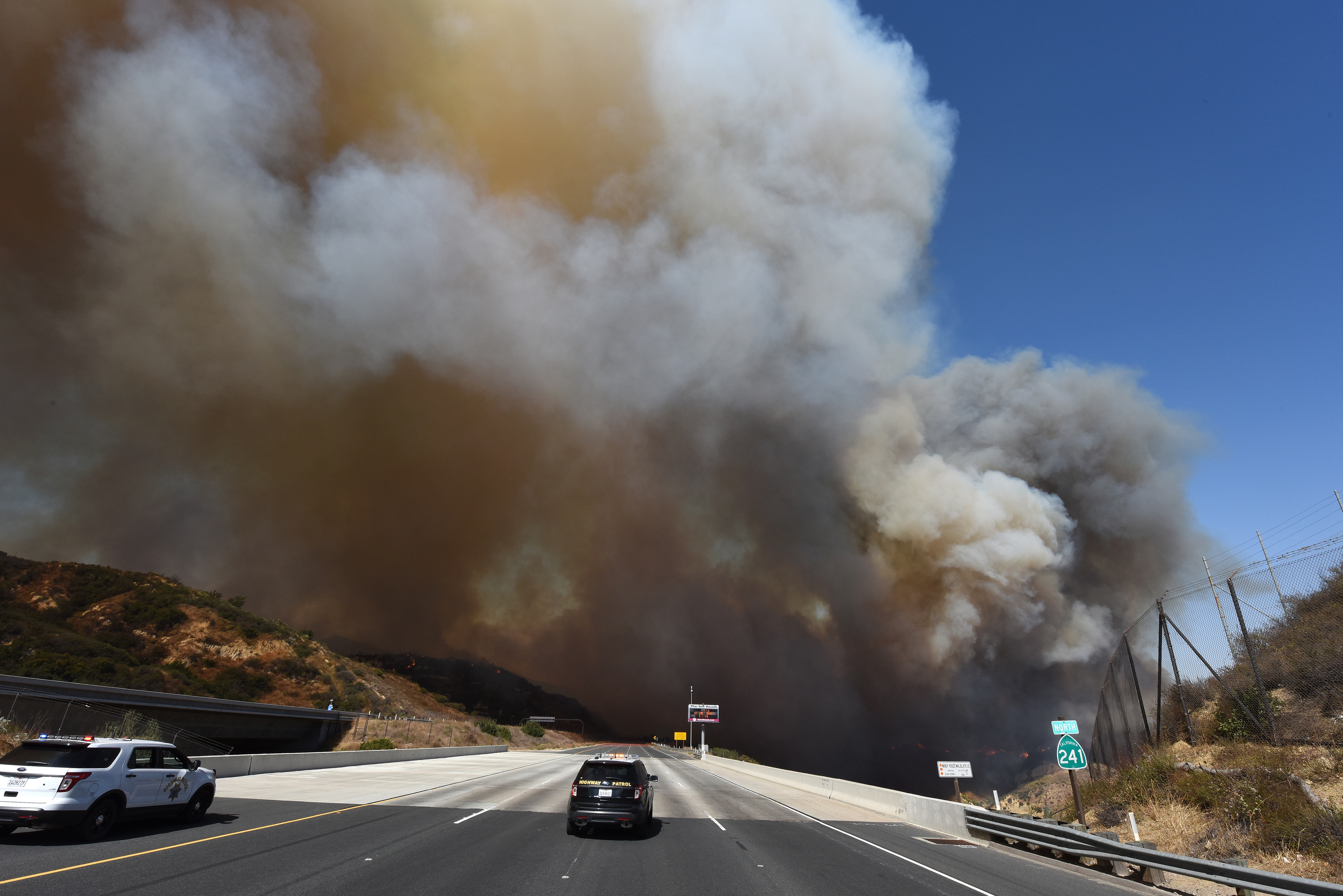 A police car blocks the 241 freeway as smoke from the Canyon 2 Fire covers the freeway near Orange, California, October 9, 2017 in Orange, California. / AFP PHOTO / Robyn Beck