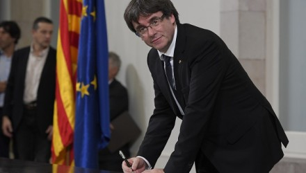 """Catalan regional government president Carles Puigdemont signs a document about  the independence of Catalonia at the Catalan regional parliament in Barcelona on October 10, 2017. Catalonia's leader Carles Puigdemont said he accepted the """"mandate of the people"""" for the region to become """"an independent republic,"""" but proposed suspending its immediate implementation to allow for dialogue.   / AFP PHOTO / LLUIS GENE"""