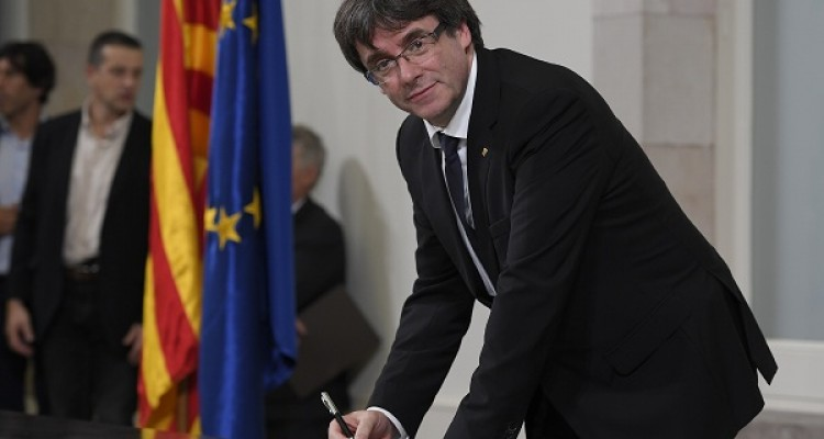 "Catalan regional government president Carles Puigdemont signs a document about  the independence of Catalonia at the Catalan regional parliament in Barcelona on October 10, 2017. Catalonia's leader Carles Puigdemont said he accepted the ""mandate of the people"" for the region to become ""an independent republic,"" but proposed suspending its immediate implementation to allow for dialogue.   / AFP PHOTO / LLUIS GENE"