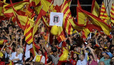 """A demonstrator holds a placard bearing a crossed-out portrait of Catalan regional leader Carles Puigdemont, who was officially ousted by Madrid, reading """"Dictators out"""" as others wave Spanish and Catalan Senyera flags during a pro-unity demonstration in Barcelona on October 29, 2017. Pro-unity protesters were to gather in Catalonia's capital Barcelona, two days after lawmakers voted to split the wealthy region from Spain, plunging the country into an unprecedented political crisis. / AFP PHOTO / LLUIS GENE"""