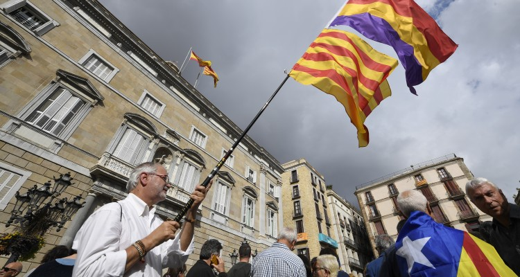 A man waves a Catalan Senyera flag along with a Spanish Tricolor flag next to a man wrapped with a Catalan pro-independence Estelada flag during a protest outside the Generalitat Palace in Barcelona on November 2, 2017 as members of the deposed Catalan government were being questioned in Madrid. Spanish prosecutors have asked that eight former members of Catalonia's deposed separatist government be jailed pending further investigation, the National Court where they are being heard said. / AFP PHOTO / LLUIS GENE