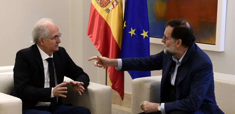 Spanish Prime Minister Mariano Rajoy speaks to former Caracas mayor Antonio Ledezma (L) during a meeting in Madrid on November 18, 2017.  Ledezma arrived from Bogota to Spain after escaping house arrest in the Venezuelan capital, after having been accused of conspiracy against the government. / AFP PHOTO / PIERRE-PHILIPPE MARCOU