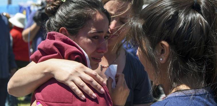 """A relative of one of the 44 crew members of Argentine missing submarine, is comforted outside Argentina's Navy base in Mar del Plata, on the Atlantic coast south of Buenos Aires, on November 23, 2017. An unusual noise heard in the ocean near the last known position of the San Juan submarine was """"consistent with an explosion,"""" Argentina's navy announced Thursday. """"An anomalous, singular, short, violent and non-nuclear event consistent with an explosion,"""" occurred shortly after the last communication of the San Juan and its 44 crew, navy spokesman Captain Enrique Baldi told a news conference in Buenos Aires.  / AFP PHOTO / EITAN ABRAMOVICH"""